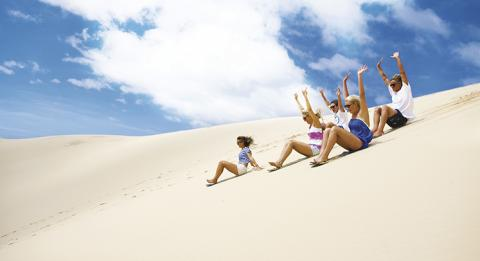 Group sandboarding down Stockton Bight Sand Dunes with Port Stephens 4WD Tours, Port Stephens