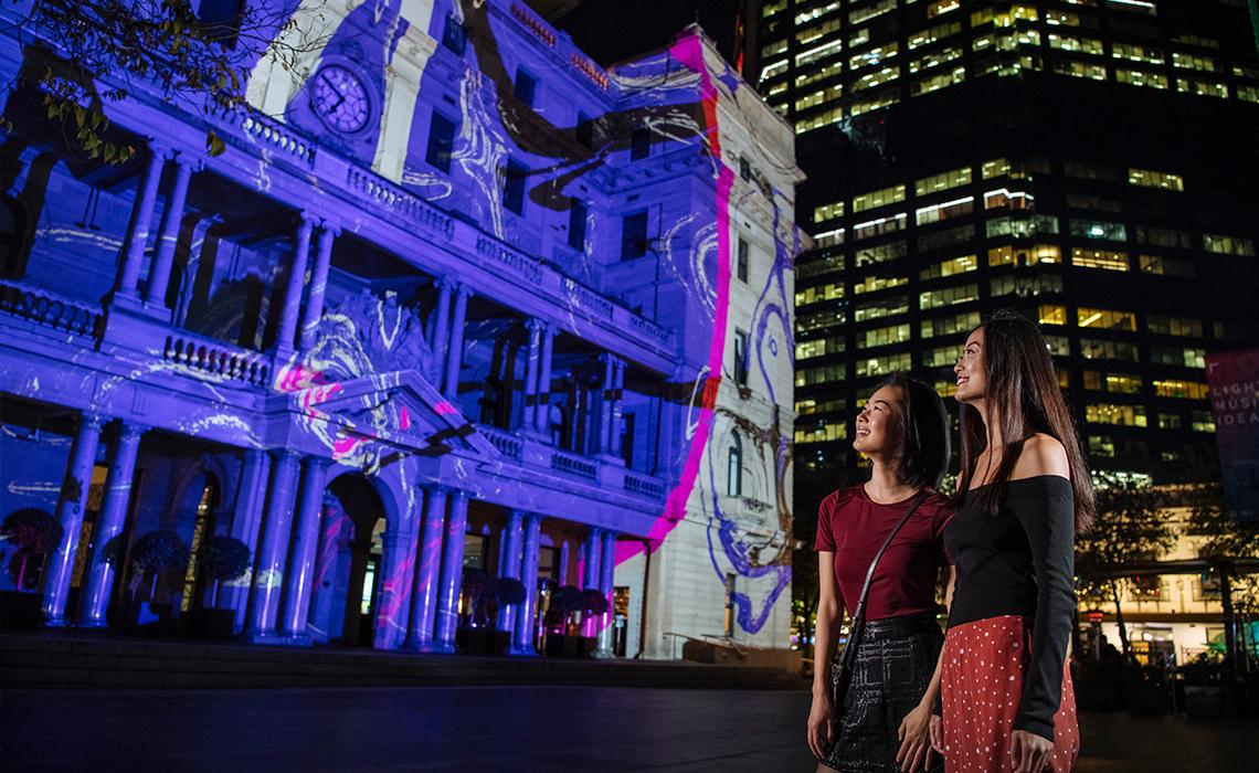 Friends enjoying the Under the Harbour light projection on Customs House during Vivid Sydney 2019.