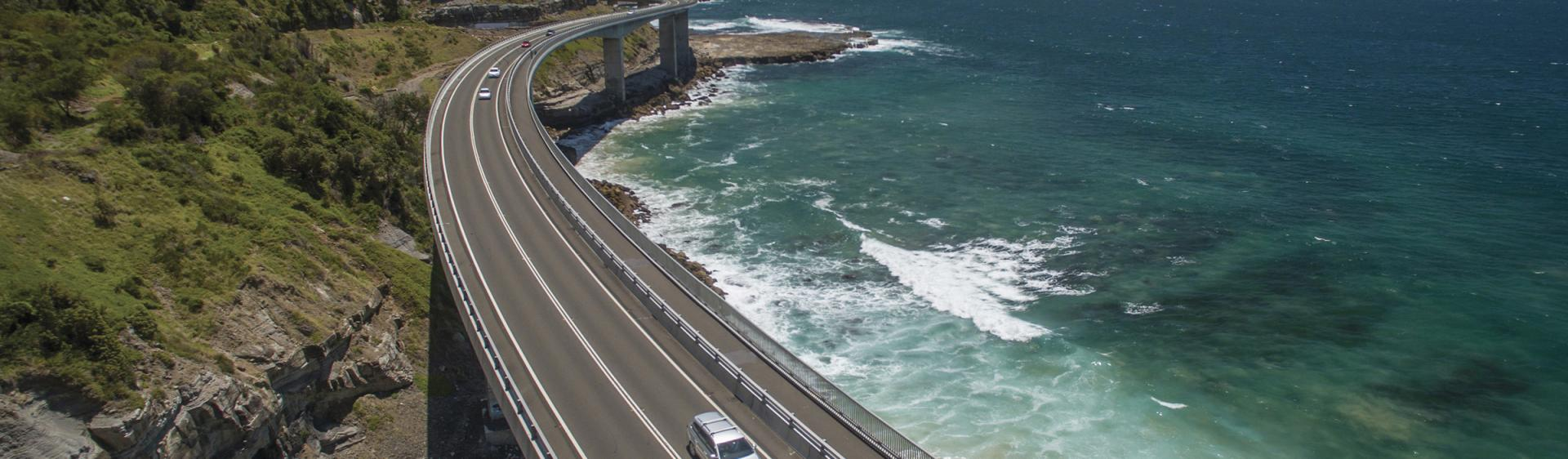 Aerial of a car taking the scenic route over Sea Cliff Bridge, Clifton