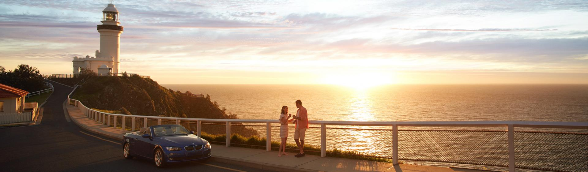 A couple enjoying sunrise at the Cape Byron Bay Lighthouse, Byron Bay.