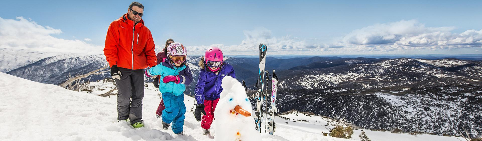 Family building a snowman at Perisher Ski Village in the Snowy Mountains after a day of skiing